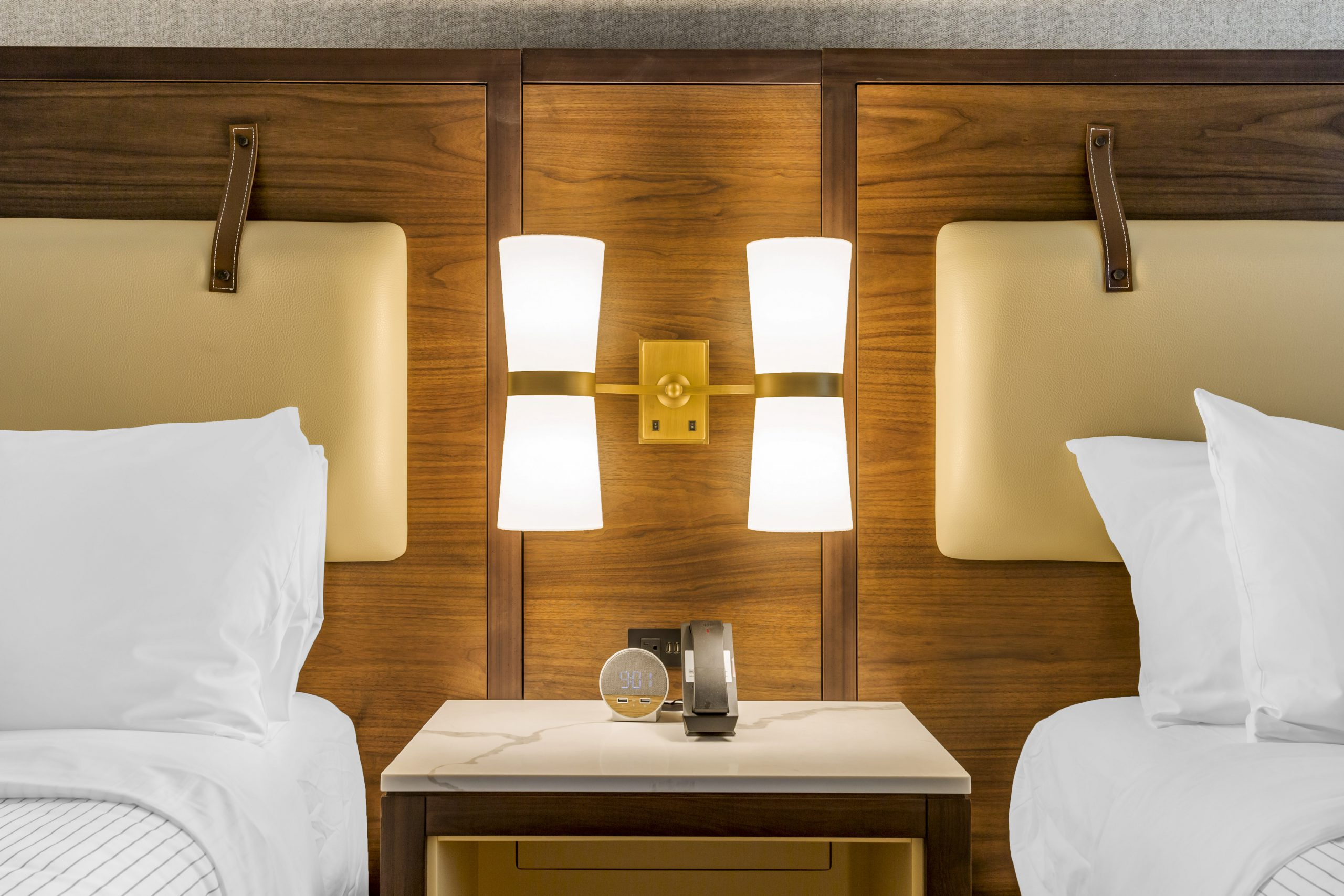 close view of two queen beds with a focus on headboards and plug in amenities
