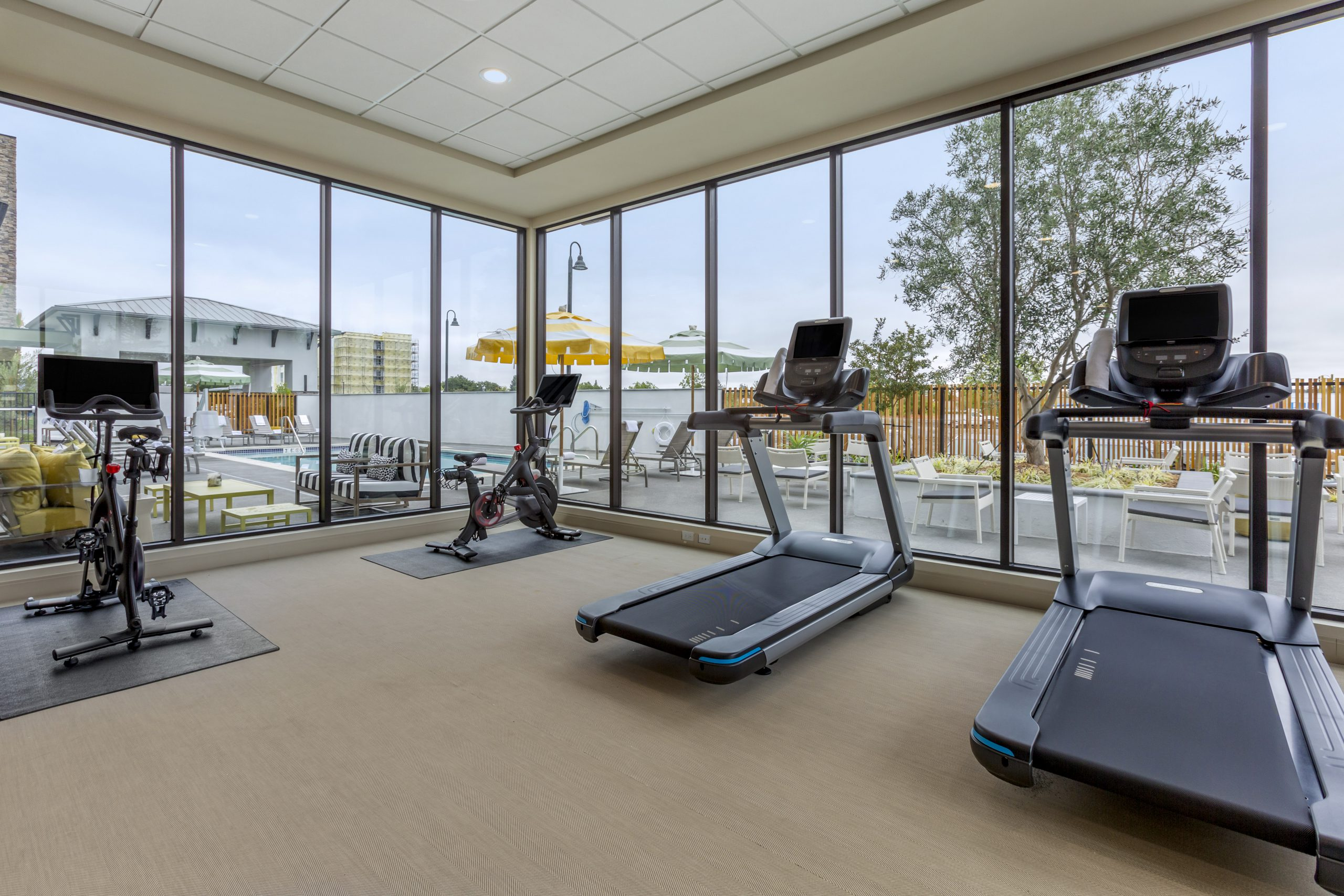 Fitness center featuring treadmills and stationary bikes with and outside view